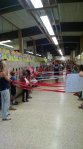 Elementary students hold streamers taut and prepare for the seniors to break through.