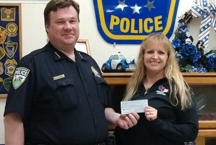 SUBMITTED PHOTO The Independent-Register Brodhead Police Chief Chris Hughes receives a check this past week from fund-raising and donations to pay for a new K9 squad car. Making the presentation is President of the local Police Association (and dispatcher) Mary Wells.
