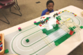 DAN MOELLER PHOTO Independent Register Brodhead Public Library 	Declan, 6, enjoys playing with one of the Lego tracks at the Brodhead public library last Thursday.