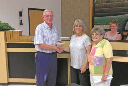 JEREMY GOKEY PHOTO Independent Register Mayor Doug Pinnow accepts a check from Brod-head Garden Club representatives Diane Anderson and Joyce Nipple to use toward replanting trees in the city parks.