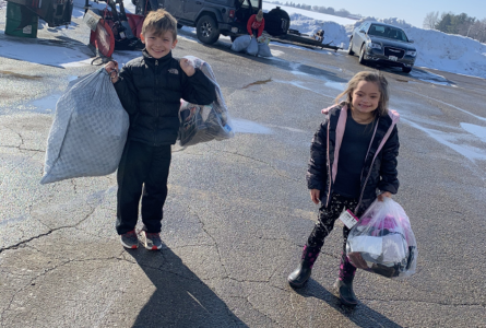 PHOTO SUBMITTED The Independent-Register Finley Riese, left, and Easton Riese help load and unload items donated for a textile drive to benefit Al-brecht Elementary School, where they are students and their mom, Lori Riese, is a third-grade teacher.